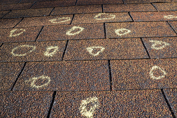 chalking up and marking hail damage on an asphalt shingle roof