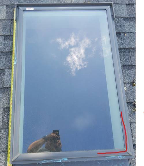 roofing contractor taking a photo of a Velux skylight with hail damage during a roof inspection