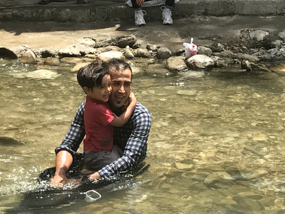 A local father and son enjoy a dip in a mountain stream to cool down from the intense summer heat