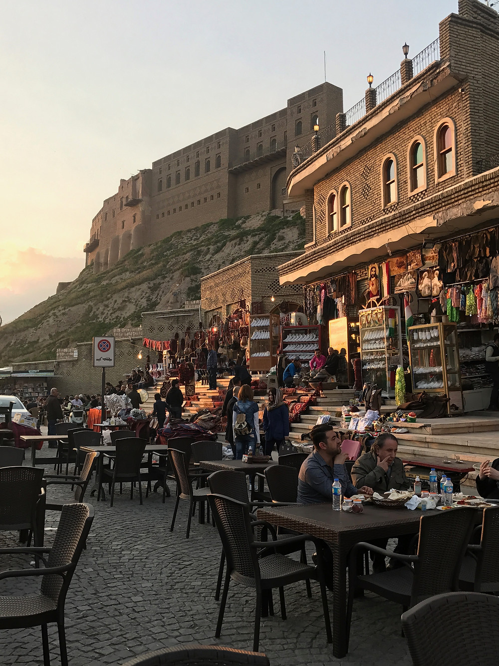 Sunset warms the walls of the Erbil Citadel, an ancient fortified city atop the tell overlooking the plaza below.