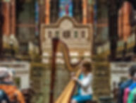Miriam Long playing concert harp for a tour in a cathedral
