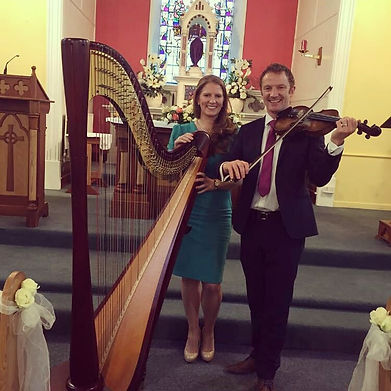 Miriam Long and Roibeard Long playing concert harp and violin at a wedding in Cork.