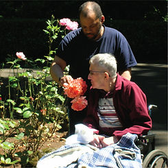 Caregiver helping client smell rouses in Our House's gardens