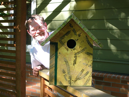 Man with hand decorated birdhouse