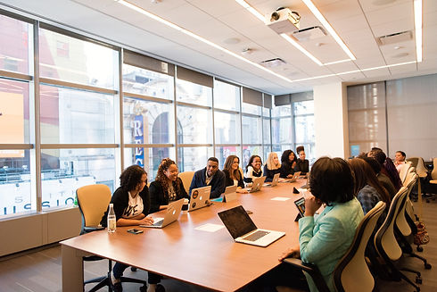 group of people sitting beside rectangular wooden table with laptops_edited.jpg