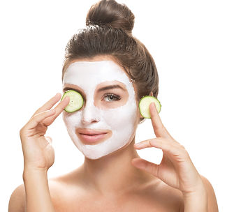 Woman with facial mask and cucumber slic