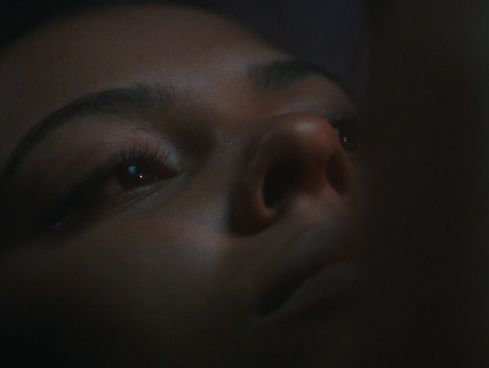 An extreme close-up of a young woman's face lit up by the dim light of her phone.