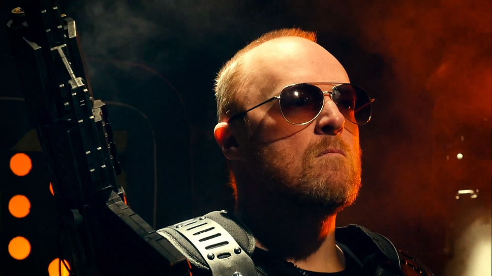 A man wearing aviator sunglasses and holding a gun, looking very determined and ready to fight.