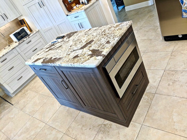 Tile floor, island with granite countertop, wood-look cabinetry, white cabinets in background.