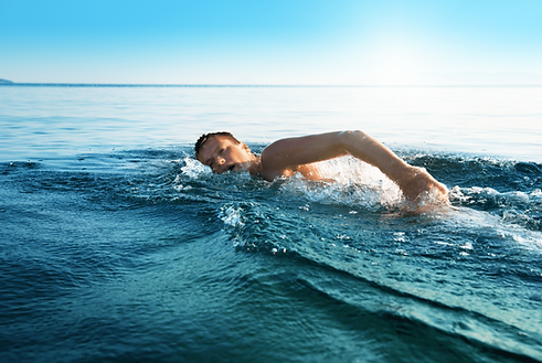 young man swimming in oceans water.jpg