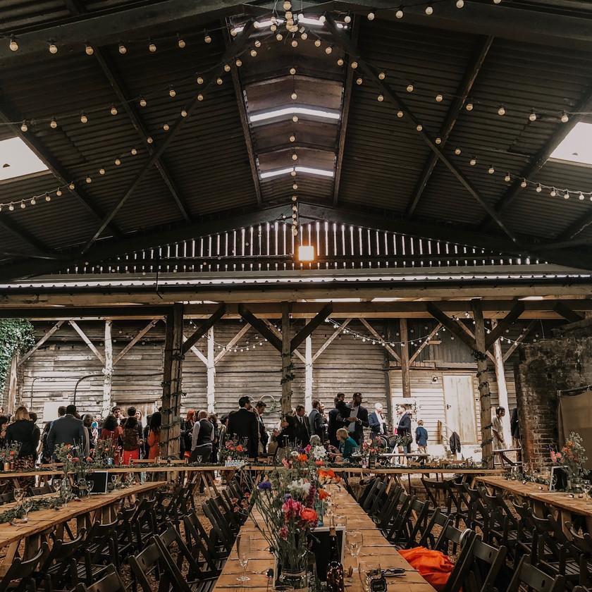 Industrial wedding reception, rustic barn, long tables