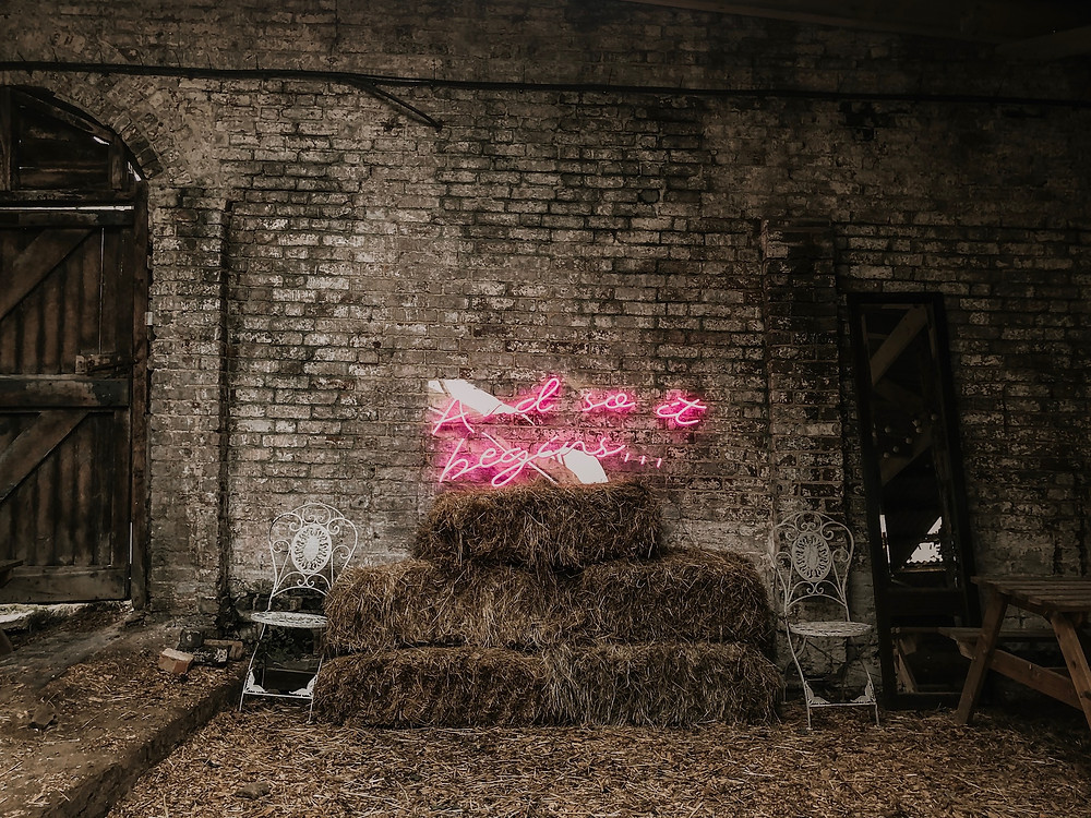 Wedding neon sign, and so it begins, rustic hay-bells and exposed brick