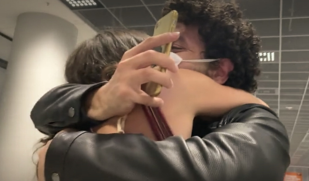 Love is not tourism, hugging couple, airport, reunited, binational couple