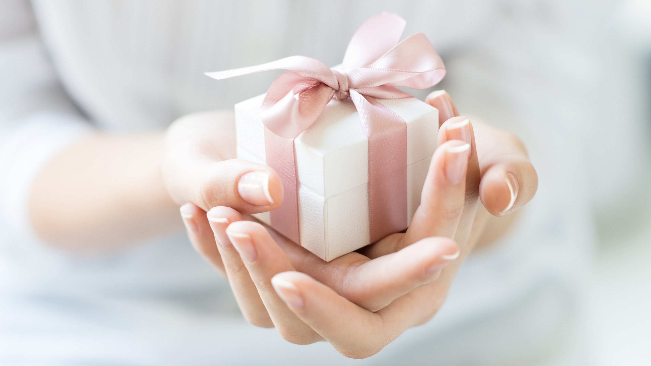 Close up shot of female hands holding a small gift wrapped with pink ribbon. Small gift in the hands