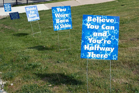 """Sign that says """"believe you can and you're halfway there"""" and """"you were born to shine"""""""