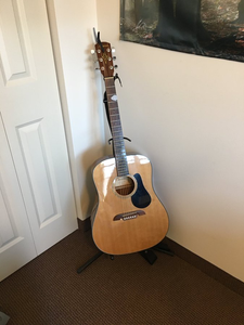 A guitar in the corner of a room.