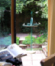 Birds on Larkrise bird table in a garden viewed from inside with bird book, binoculars, coffee and a biscuit on the table