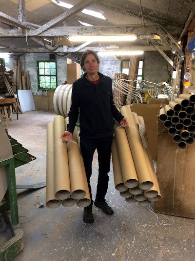 Billy with large cardboard tubes he has made for us
