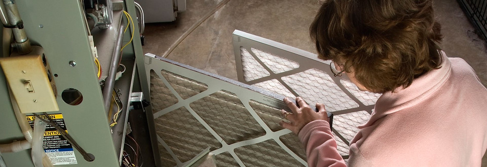 Woman changing furnace filters.