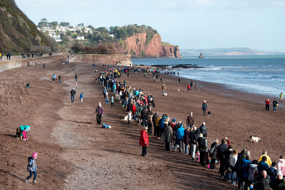 The human chain forming on Teignmouth beach