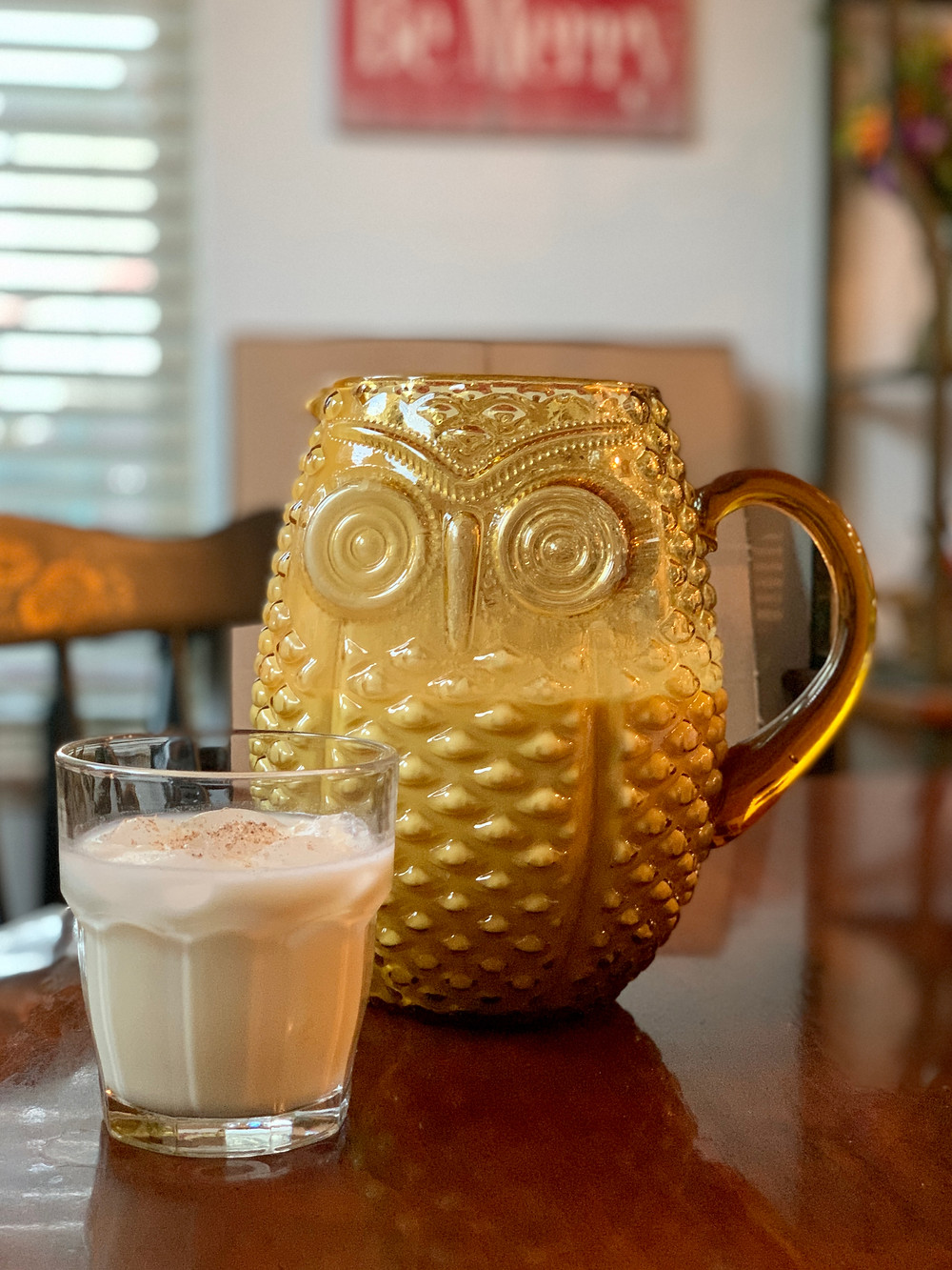 Yellow glass owl pitcher and glass of coquito on a table