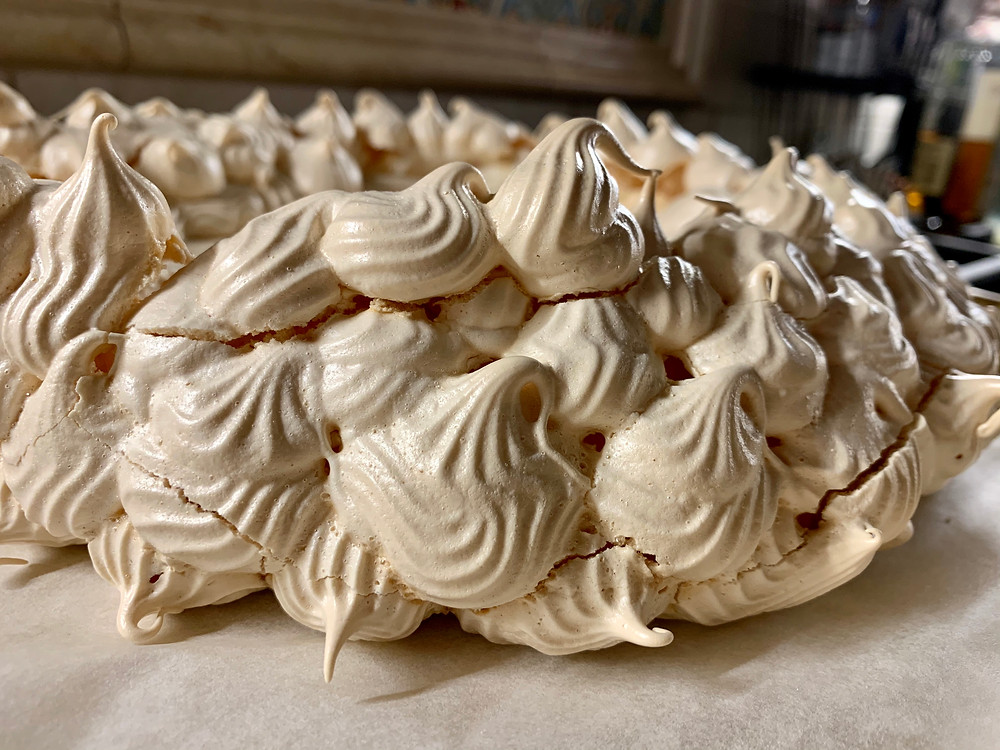 The fully baked meringue out of the oven. It is very light golden brown with small cracks.