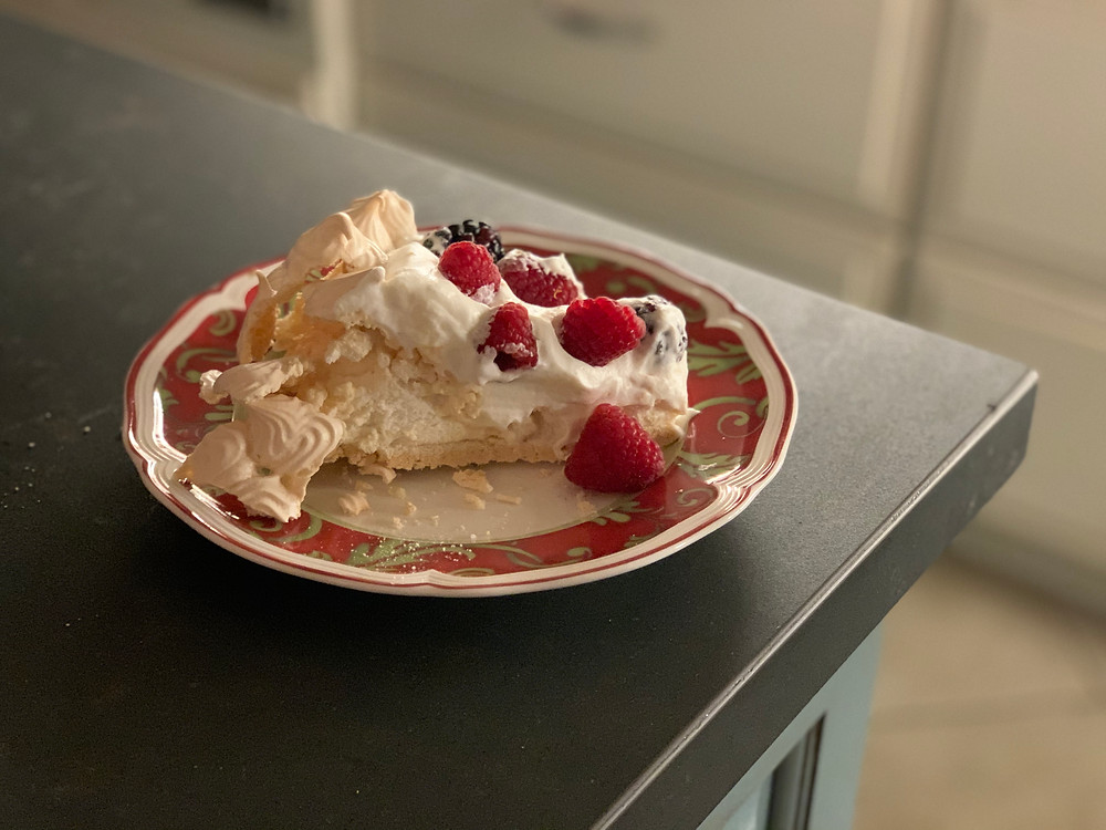 A slice of pavlova on a white plate with a red and green swirled rim, on the corner of a matte black countertop.