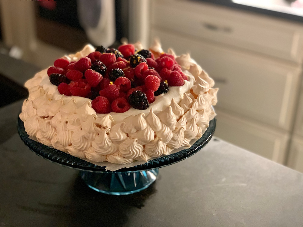A finished pavlova, topped with raspberries and blackberries, on the corner of a black countertop.