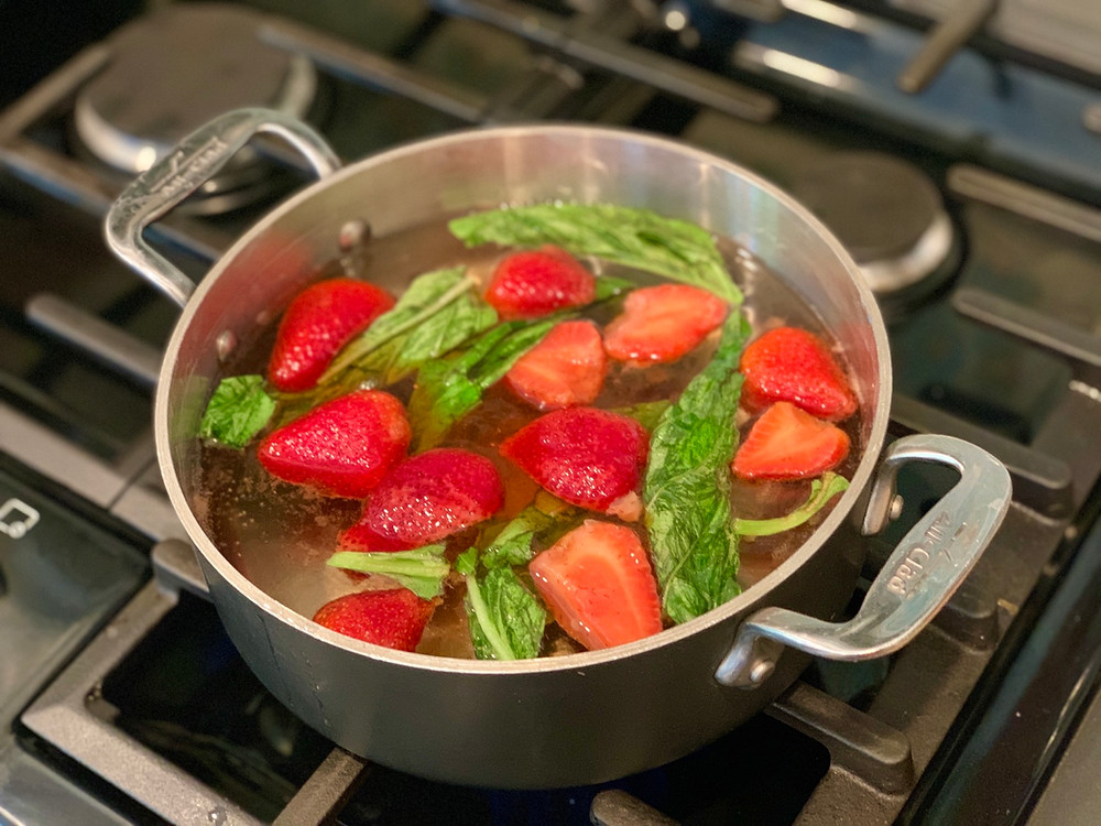Sliced strawberries and basil leaves in a small, shallow pot of clear liquid on the stove.