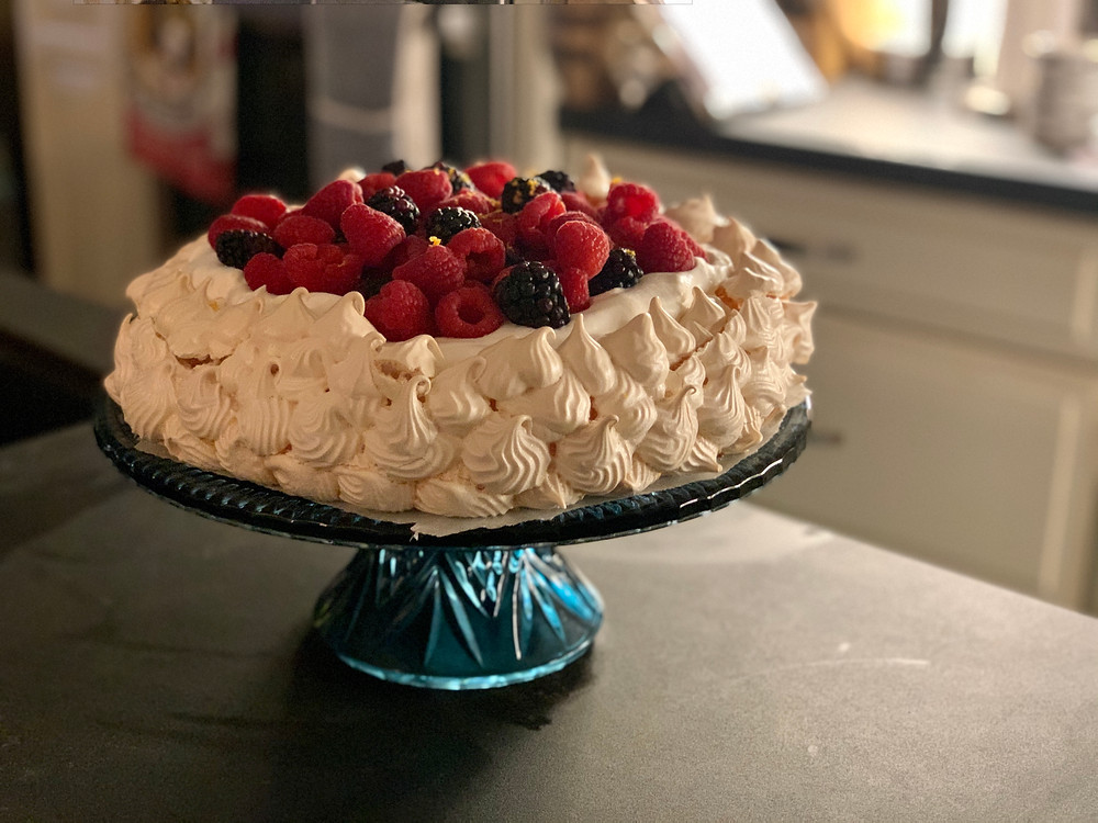 The finished pavlova on a matte black countertop.