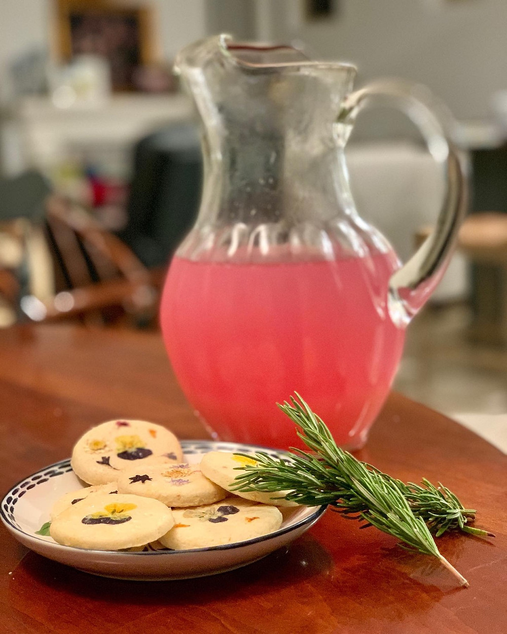 Bright pink liquid in a clear glass pitcher. In front of the pitcher, there is a small plate of sugar cookies with dried flowers baked into the tops. There are two sprigs of rosemary propped against the plate at a diagonal. The background is blurred.