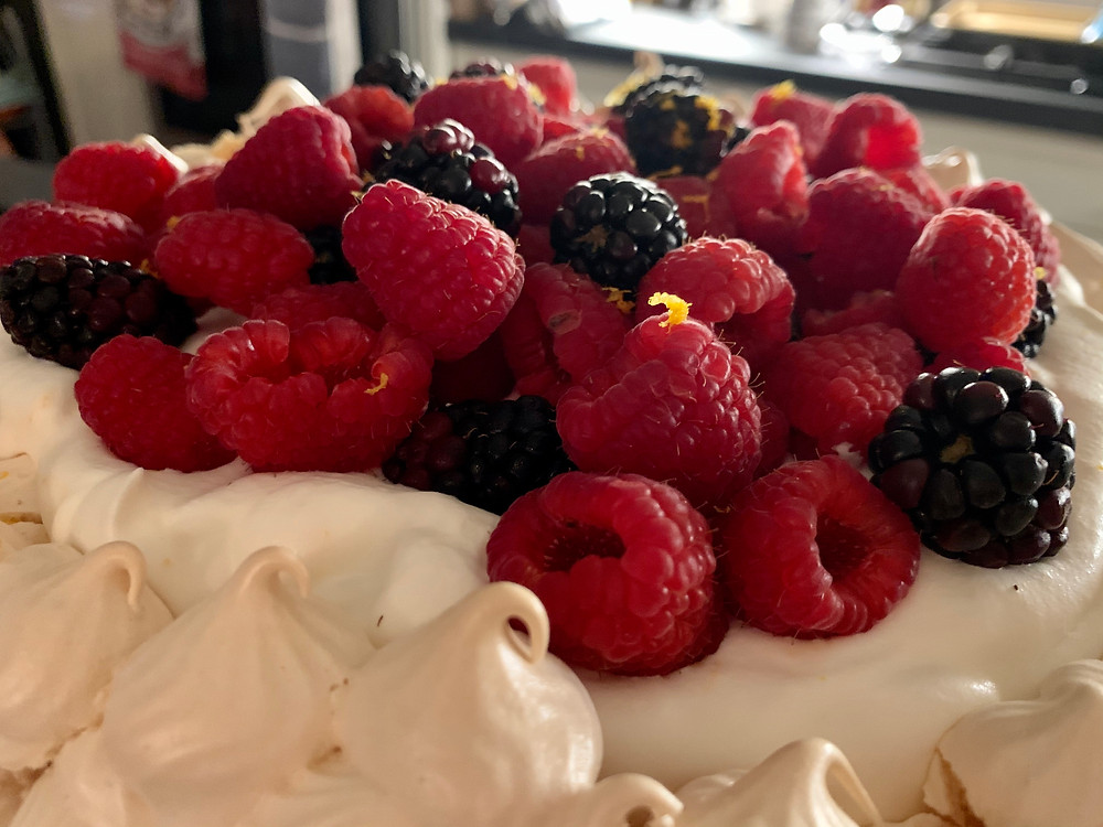 A closeup of raspberries, blackberries, and orange zest on top of a pavlova.