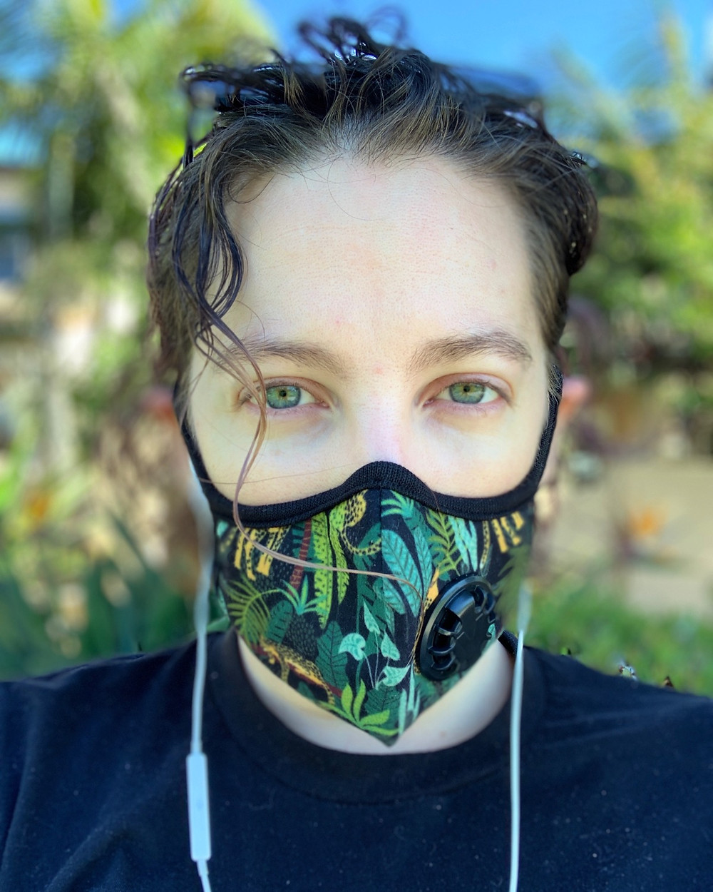 Pale woman with green eyes and dark brown curly hair. Her hair is tied back and she has sunglasses on the top of her head. She's wearing a jungle print N95 mask. The background is blurred and she is outside on a sunny day.