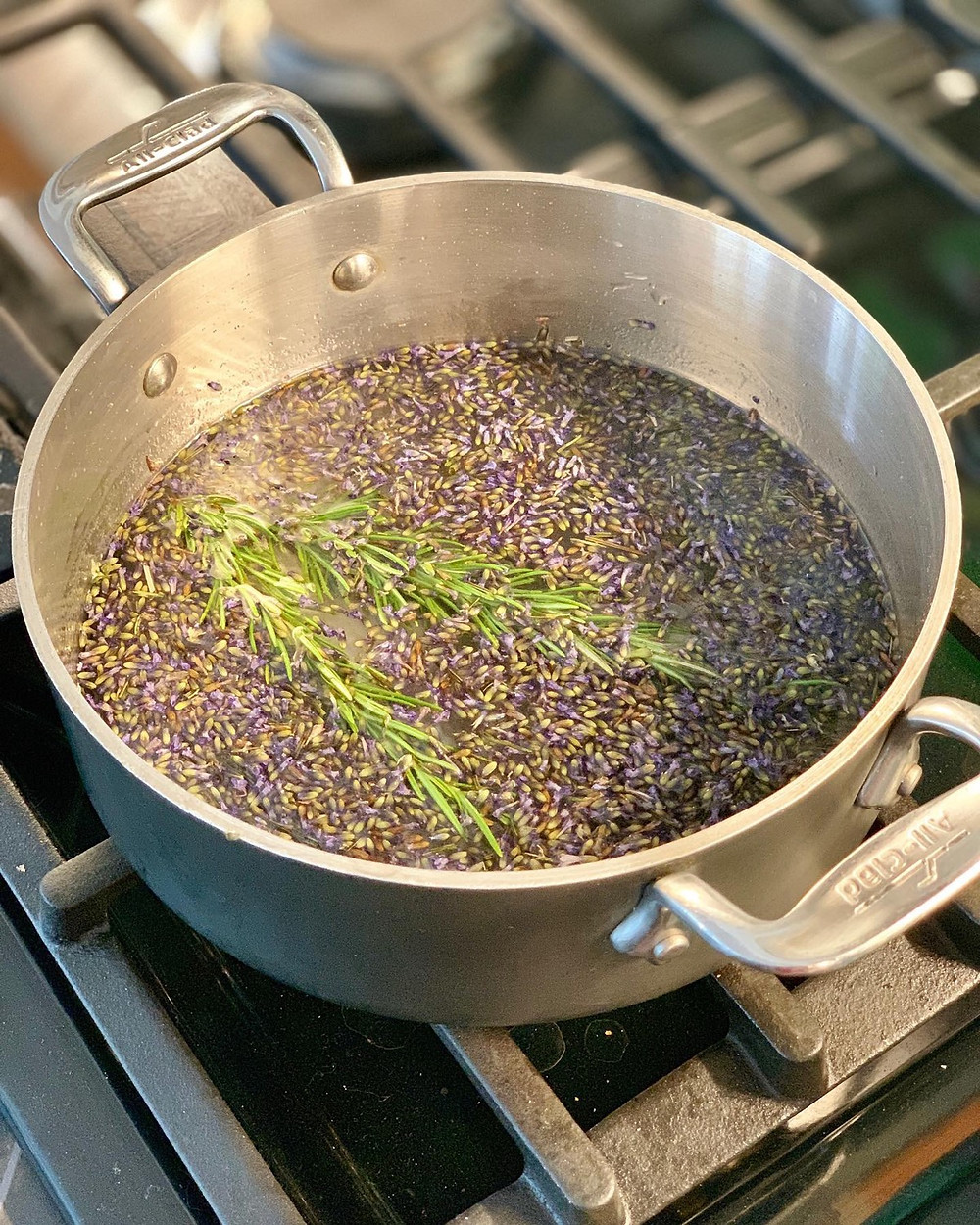 Dried lavender and two sprigs of rosemary in a small, shallow pot on the stove. They are floating in dissolved sugar and water.