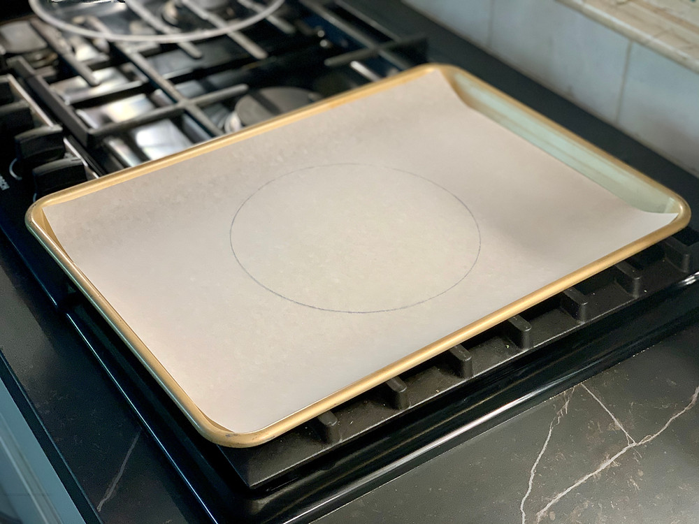 A circle drawn onto a piece of parchment paper in a gold colored baking sheet. It is sitting on an unlit stove.