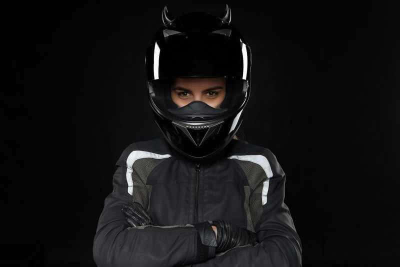 Motorcycle sports, extreme, competition and adrenaline. Active young female racer wearing protective helmet and uniform going to participate in road racing or motorcross