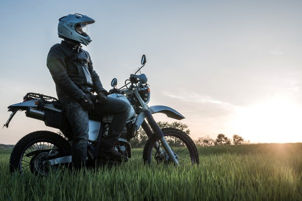 dual sport rider with his motorcycle parked on the grass enjoying the sunset.jpg