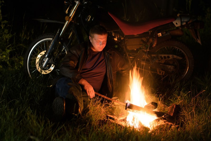 motorcycle campfire and a rider sitting next to it