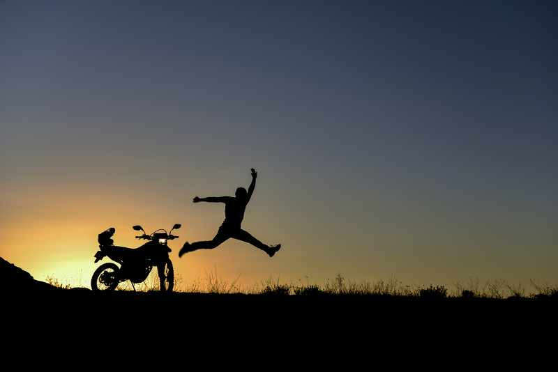 happy biker jumping with a sunset background
