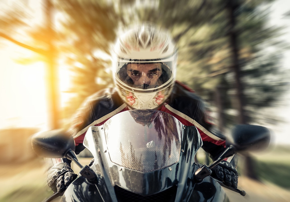 motorcyclist with helmet and apparel facing forward while he rides