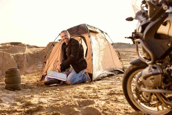 motorcycle rider camping next to his bike in the desert