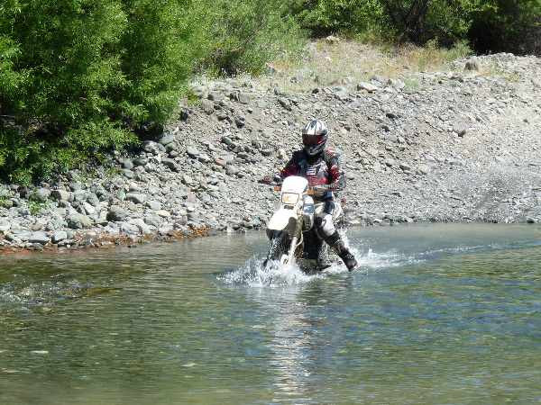 enduro motorbike crossing a river