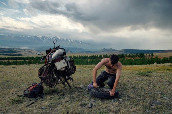 a motorcycle adventure rider fixing his tire