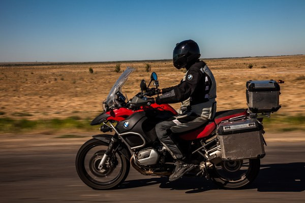 a motorbike rider with luggage riding on the road in full uniform.JPG