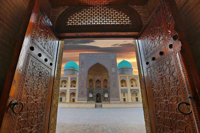 View to Mir i Arab madrassa thru the old wooden carved door, Bukhara, Uzbekistan_800x534