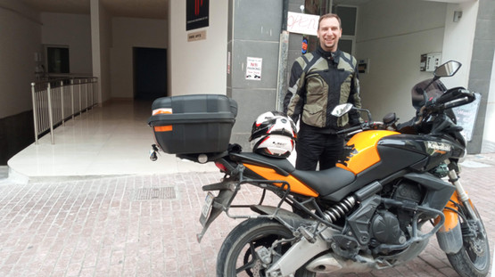 standing in front of his bike wearing siima sibirsky suit