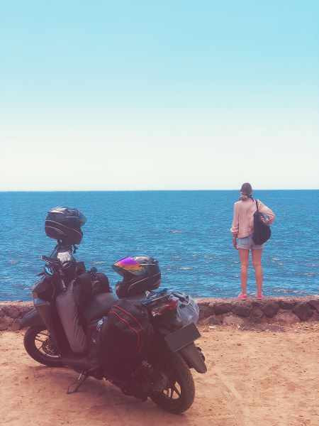 a person standing in front of the sea with a backpack and a motorcycle next to him_450x600.jpg