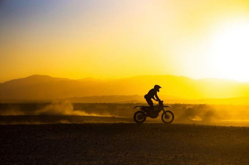 motorcycle_rider_standing_while_riding_in_to_the_sunset_800x533