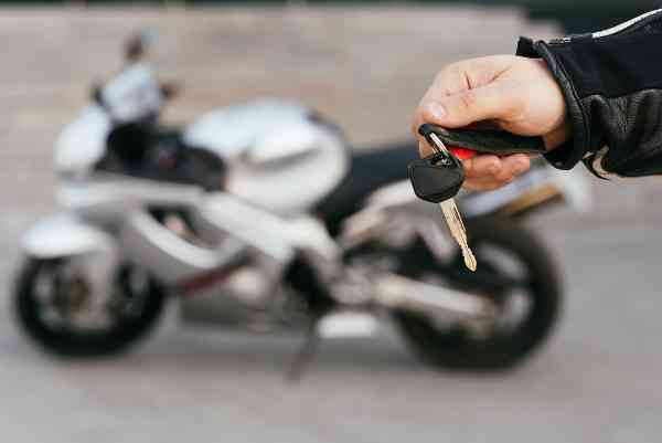 holding the motorcycle keys with silver motorbike at the back