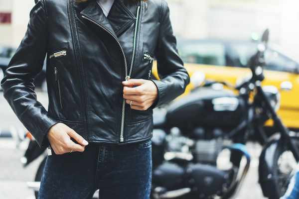 a woman zipping her leather jacket in front of a motorcycle